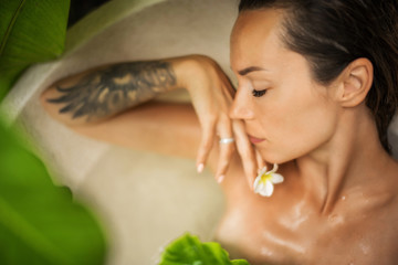Woman relaxing in outdoor bath with tropical leaves at Bali