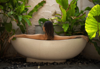 Obraz Woman relaxing in outdoor bath with tropical leaves at Bali - fototapety do salonu