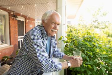 Senior man drinking lemonade on porch