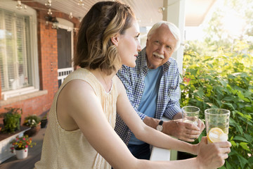 Senior father and daughter drinking lemonade on porch