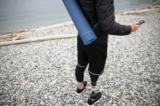 Male amputee with yoga mat using smart phone on beach