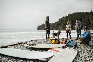 Friends with dog enjoying weekend surfing getaway next to surfboards on rugged beach