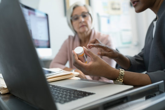 Female doctor prescribing mediation to senior patient in clinic office