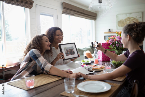 Daughters photographing mother with Mothers Day framed photograph gift