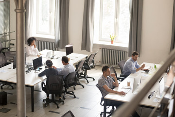 Diverse employees busy working together in shared office