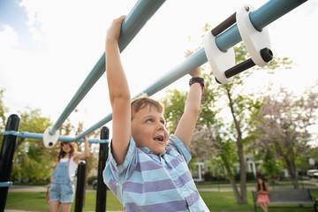 Playful boy swinging from monkey bars at playground