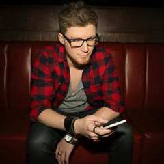Male hipster millennial texting with smart phone in nightclub
