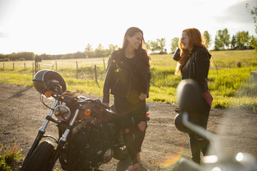 Smiling women friends talking at motorcycle on sunny rural road