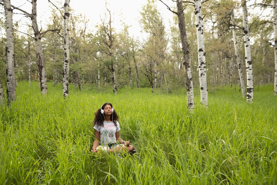 Serene young woman with headphones meditating in tall grass in woods