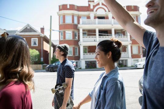 Millennial friends walking on sunny neighborhood sidewalk