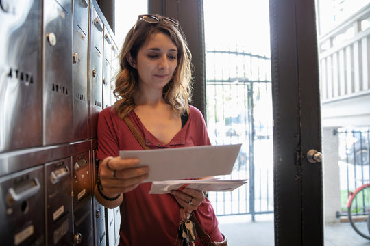 Young woman checking mailbox in apartment entrance