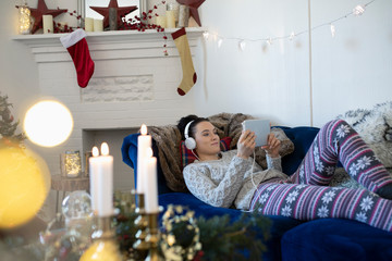 Young woman with headphones relaxing, watching movie with digital tablet in Christmas living room