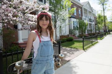 Portrait confident, cool girl holding skateboard on sunny neighborhood sidewalk