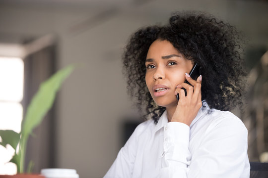 Pensive black woman talk over cell making decision