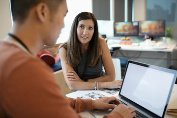 Creative businessman and businesswoman using laptop in office