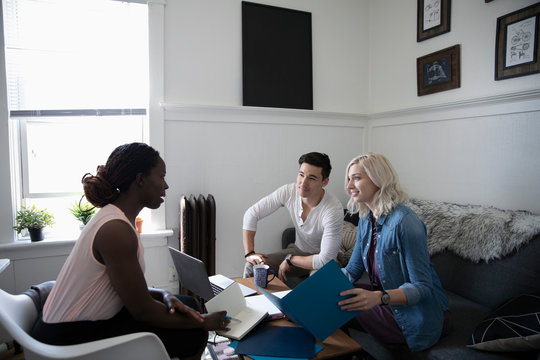 Financial advisor consulting with young couple in living room