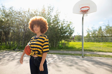 Portrait confident, cool teenage girl with afro playing basketball at park basketball court