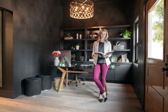 Portrait female designer working in dark, creative office