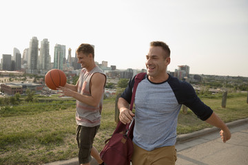 Gay male couple with basketball in urban park