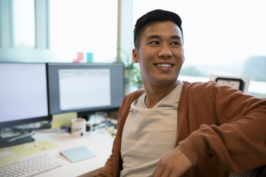 Smiling businessman looking away in office