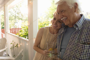 Affectionate senior father and daughter hugging and drinking lemonade on porch