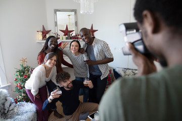 Young man with instant camera photographing friends in Christmas living room
