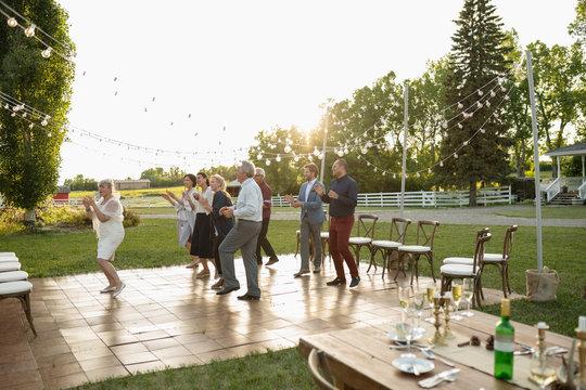 Friends dancing, celebrating at wedding reception in rural garden