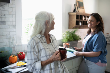 Smiling daughter and senior mother drinking tea and cooking, cutting vegetables in kitchen