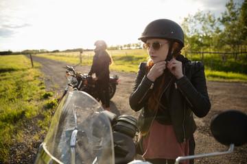 Woman fastening motorcycle helmet on sunny rural road