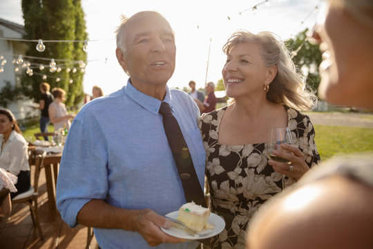 Affectionate couple eating cake and drinking wine, celebrating anniversary at sunny, rural garden party