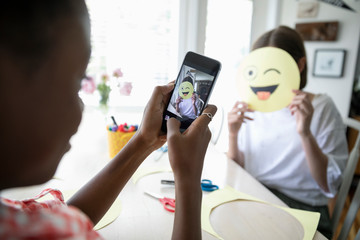 Tween girl with camera phone photographing friend holding winking emoji art project