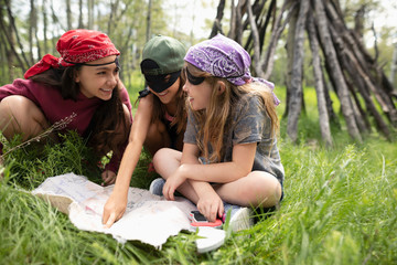 Girl friends in pirate costumes looking at treasure map in woods