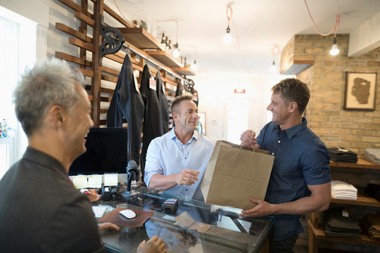 Gay male couple shopping in clothing store, making purchase at counter