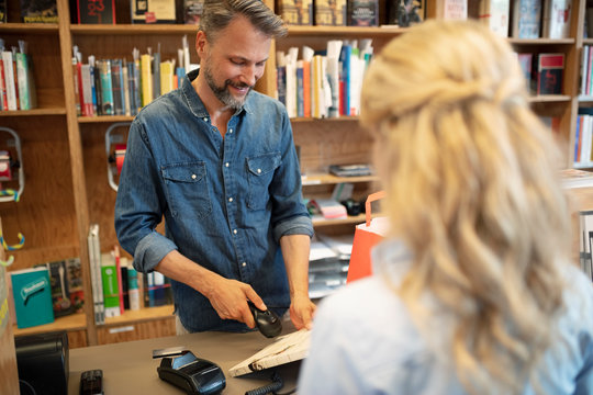 Male bookstore cashier scanning barcode on book