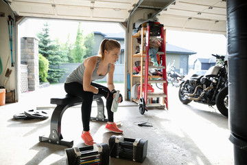 Young woman weightlifting, resting in garage