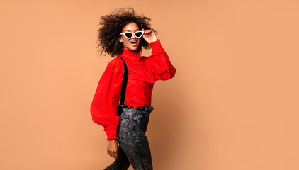 Horizontal fashion  image of excited black woman jumping with happy face expression on beige background. Wearing vintage red shirt