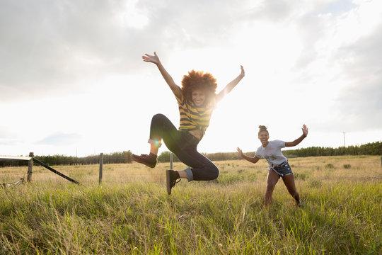 Portrait playful teenage girl friends jumping in sunny rural field