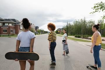 Teenage girls skateboarding on neighborhood street