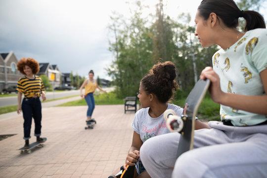 Teenage girl friends skateboarding in neighborhood park