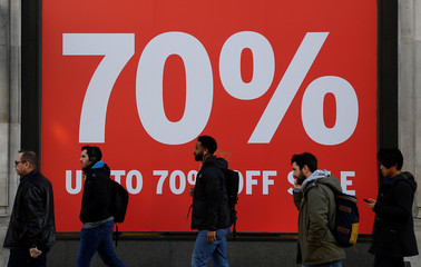 Pedestrians pass a sale sign on a retail shop on Oxford Street in London