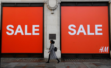 A woman walks past a sale sign on a branch of H&M on Oxford Street in London