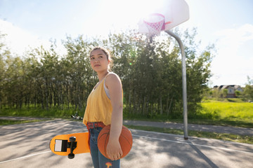 Confident, cool teenage girl with skateboard and basketball on sunny park basketball court