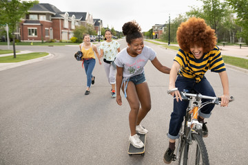 Playful teenage girls skateboarding and bike riding on neighborhood street