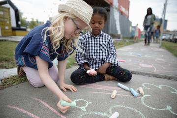 Girls coloring with sidewalk chalk