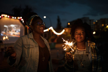 Happy young women with sparklers at movie in the park