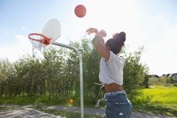 Young woman playing basketball at park basketball court