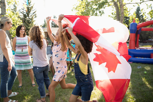 Girls waving Canadian flag on Canada Day summer neighborhood block party in park