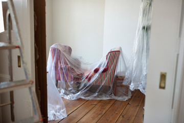 Drop cloth over furniture in room being painted