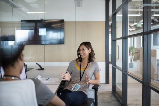 Smiling businesswoman talking with colleague in conference room meeting