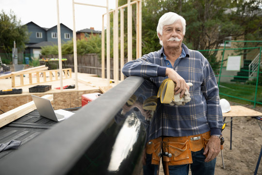 Portrait confident senior man working at construction site, leaning on truck